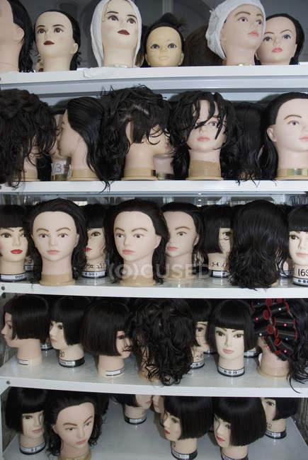 Perucas em manequins em prateleiras — Fotografia de Stock