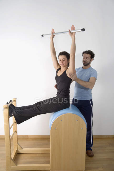 Instructor adjusting posture of woman exercising on pommel horse — Stock Photo