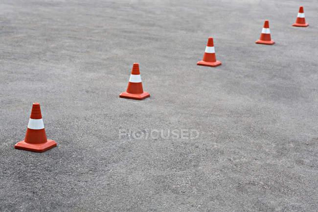 Fila de conos de naranja sobre asfalto - foto de stock