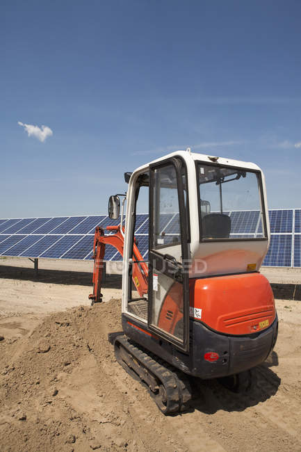 Digger vehicle on solar panel construction site — Stock Photo