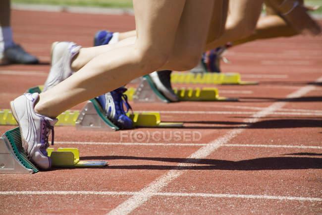 Baixa seção de atletas com pés em blocos iniciais na pista de corrida — Fotografia de Stock