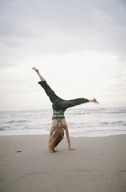 Задній вид жінки роблять колесо на пляжі — стокове фото