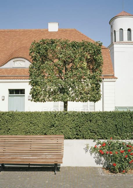 Edifício atrás das sebes e árvores do topiary branco — Fotografia de Stock