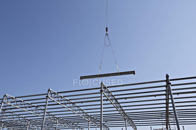 Kran senkt Stahlträger in Richtung Baugerüst — Stockfoto