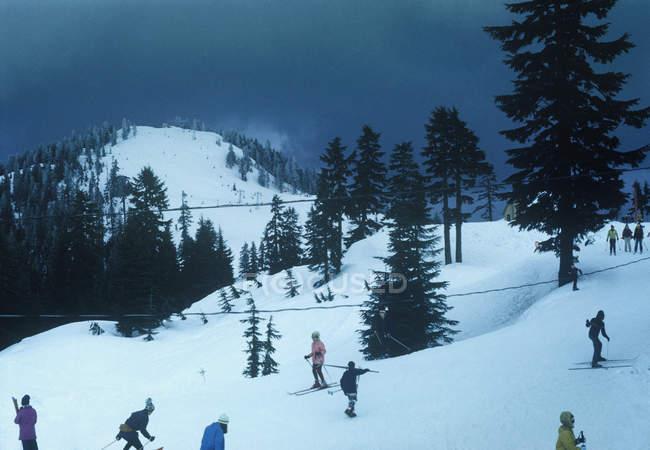 Gens faire du ski dans une station de ski — Photo de stock