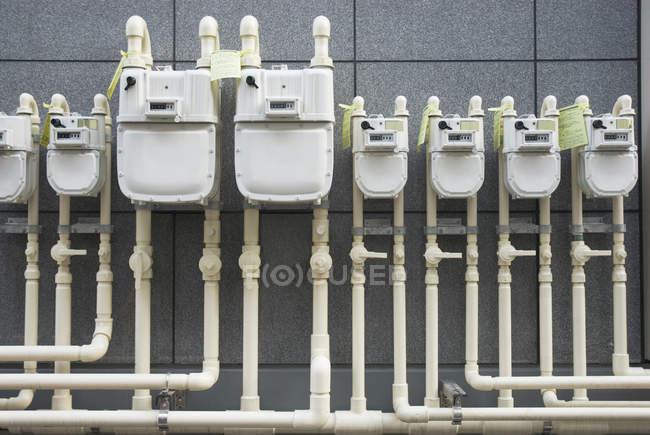 Fila de contadores de gás industriais na parede — Fotografia de Stock