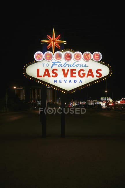 Iluminado Bienvenido a Las Vegas signo en la carretera de noche - foto de stock
