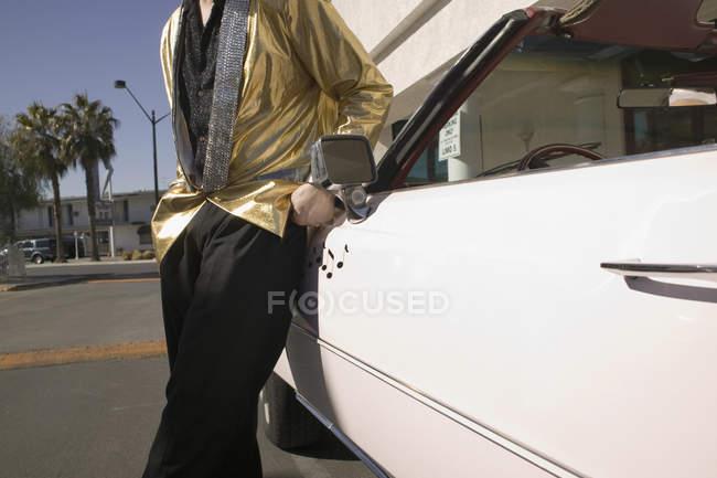 Person in goldener Jacke lehnt an Oldtimer-Cabrio — Stockfoto