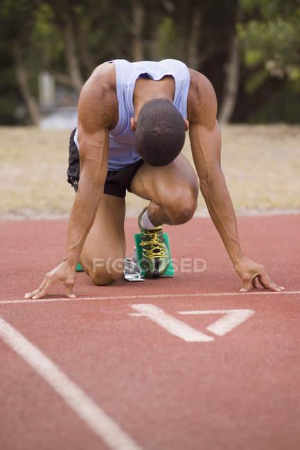 Atleta masculino en los tacos de salida en la pista de atletismo - foto de stock