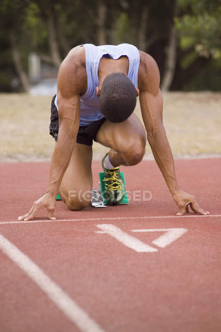 Male athlete at starting blocks on running track — Stock Photo