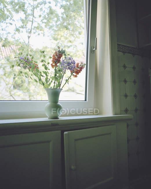 Flores em vaso cerâmico no peitoril da janela — Fotografia de Stock