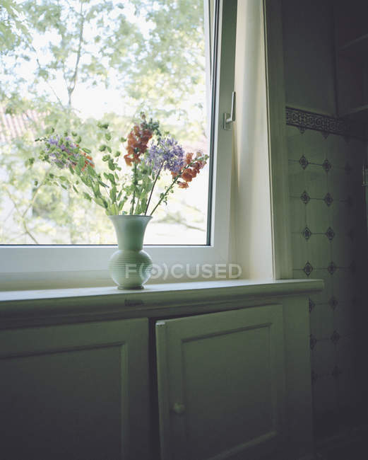 Flowers in ceramic vase on window sill — Stock Photo