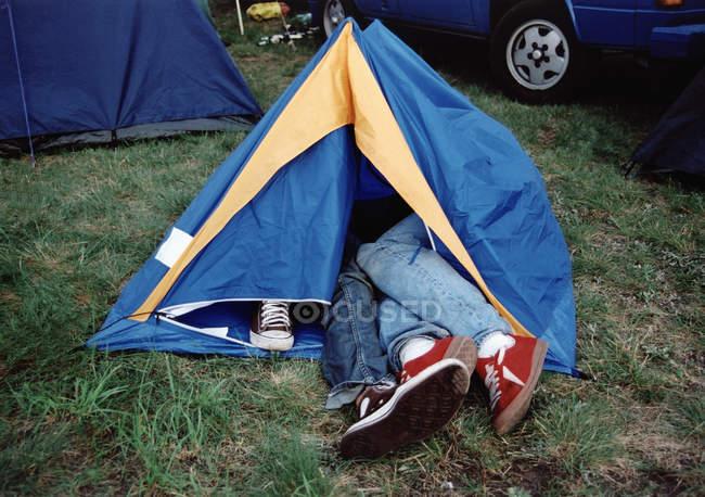 Pernas saindo de uma pequena tenda turística — Fotografia de Stock