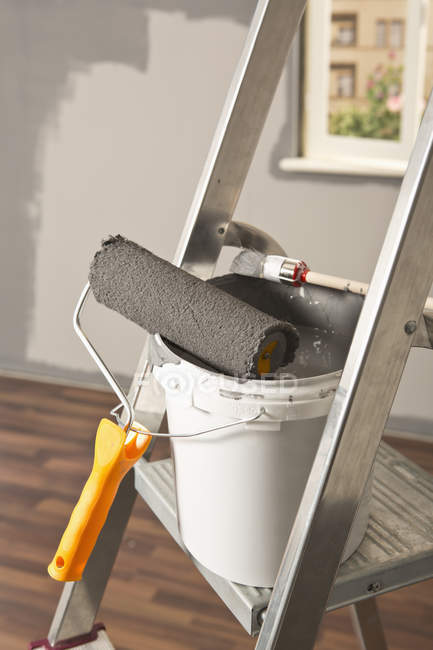 Ladder with paint roller and paintbrush leaning on paint bucket — Stock Photo