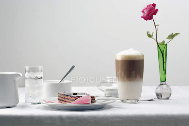 Breakfast cake and coffee on table with vase — Stock Photo