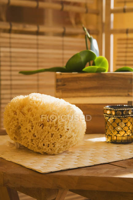 Bath sponge and candle on table — Stock Photo