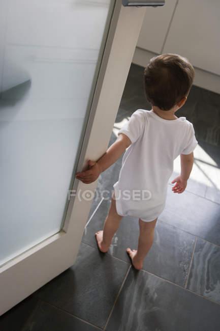 Вид сзади маленького мальчика, стоя внутри проема — стоковое фото