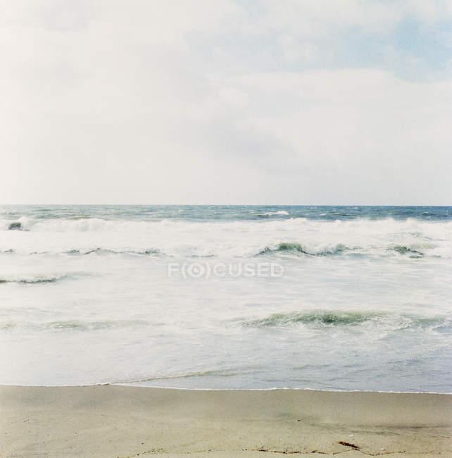 Vue tranquille sur les vagues de l'océan vue de la plage — Photo de stock