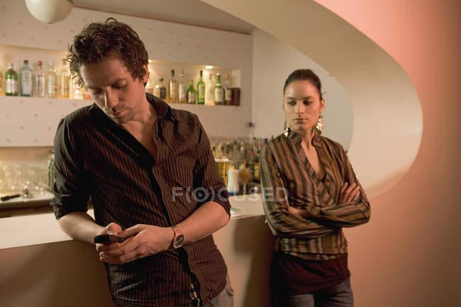Homem encostado contra a barra de mensagens de texto, enquanto a mulher está sozinha com os braços cruzados — Fotografia de Stock