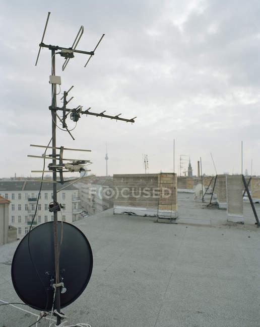 TV antena y antena parabólica en la azotea del apartamento - foto de stock