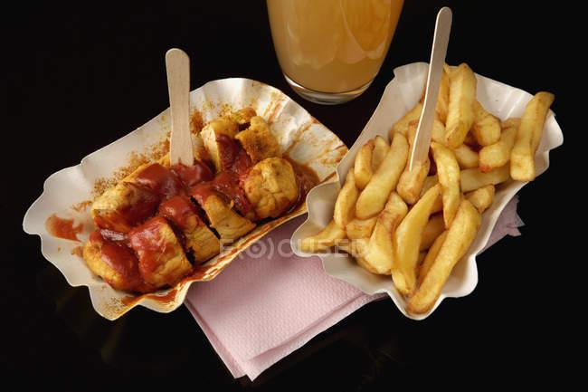 Карривурст и картофель фри с кетчупом на черном фоне — стоковое фото