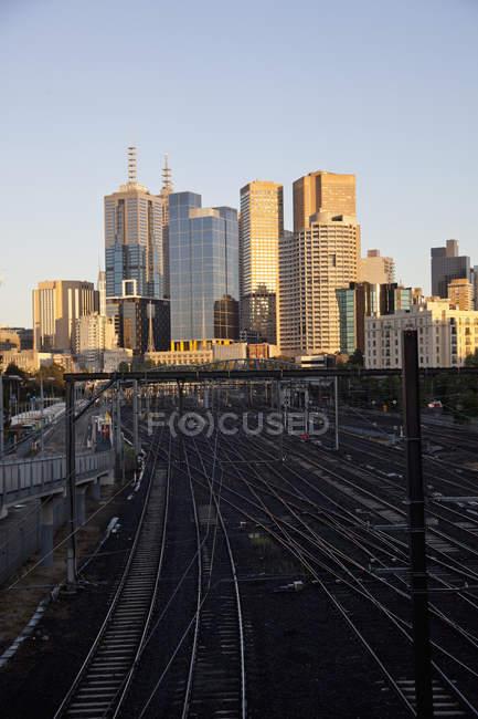 Vue des voies de train et les bâtiments de la ville ensoleillée — Photo de stock