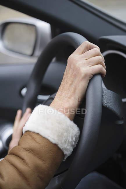 Mains femelles de récolte sur volant de voiture — Photo de stock