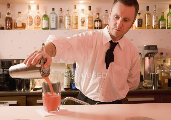 Bartender pouring a cocktail into a glass — Stock Photo