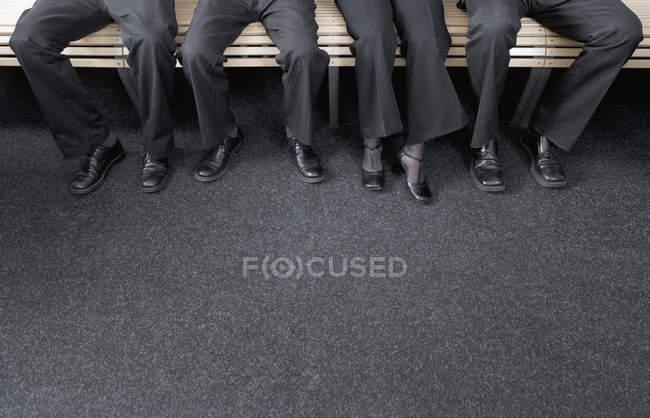 Close-up de quatro homens de negócios e mulher de negócios sentados no banco juntos — Fotografia de Stock