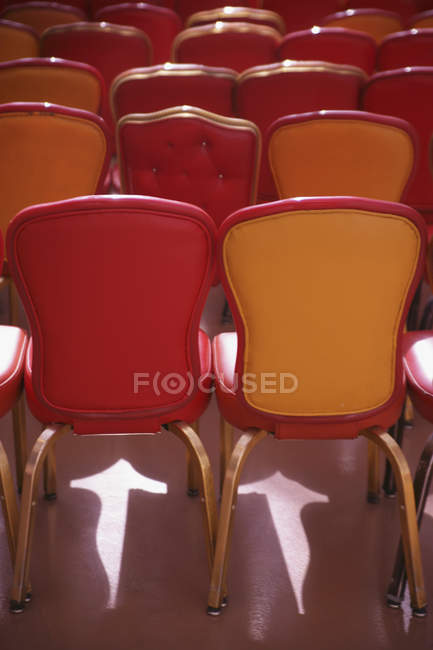 Red and beige chairs under spotlight in auditorium — Stock Photo