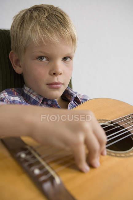 Молодий хлопчик сідаючи і грав на гітарі — стокове фото