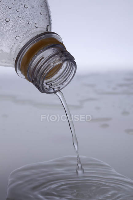 Colheita garrafa de plástico derramando água para fora — Fotografia de Stock