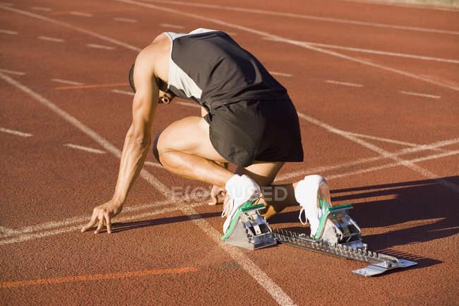 Atleta masculino en bloques a partir de una pista de atletismo - foto de stock