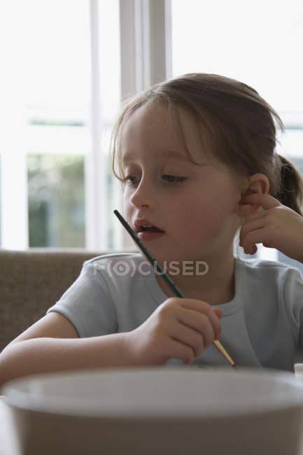 Вдумчивая маленькая девочка, держащая кисть, сидя на стуле — стоковое фото