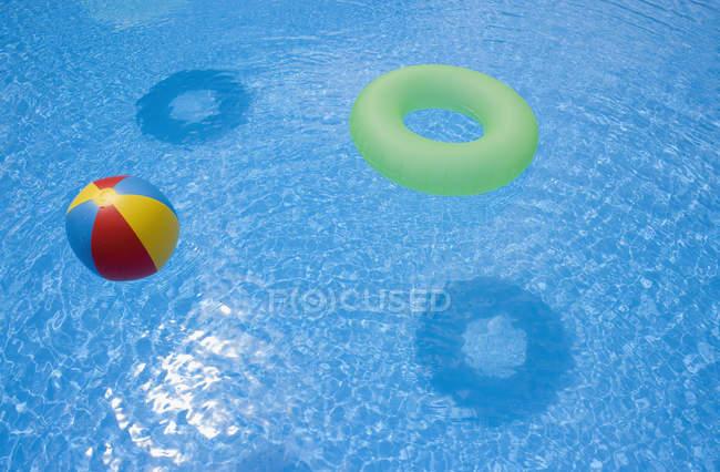 Bola inflável e anel flutuando na piscina — Fotografia de Stock