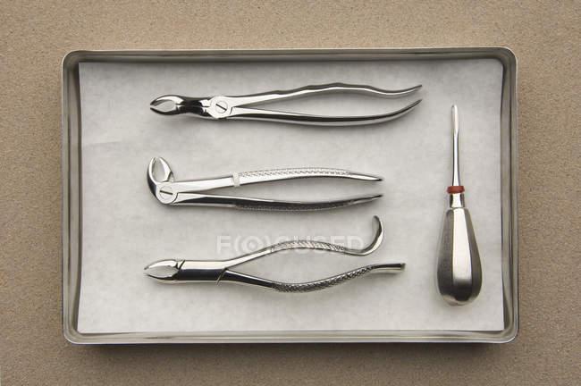 Pinces dentaires et levier sur un plateau en métal — Photo de stock