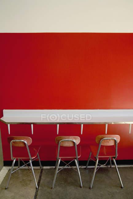 Три порожніх табурети за прилавком в кафе — стокове фото