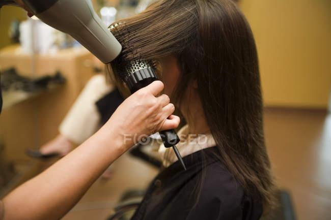 Main de récolte sécher les cheveux féminin au salon — Photo de stock