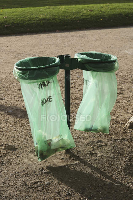 Plastic garbage bags in holders at park alley — Stock Photo