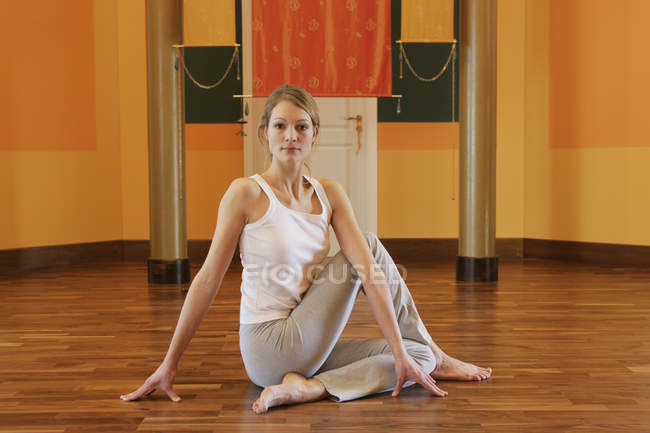Young woman stretching on floor — Stock Photo