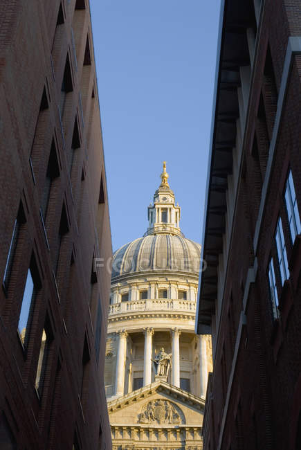 Bottom view of St. Paul's Cathedral between buildings, London, England — Stock Photo