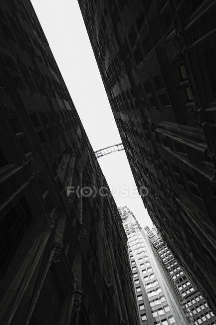 Vista inferior del puente peatonal entre dos fachadas de edificio - foto de stock