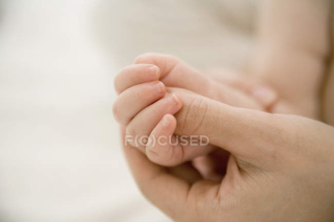 Обрезать руку матери, массируя руку ребенка — стоковое фото