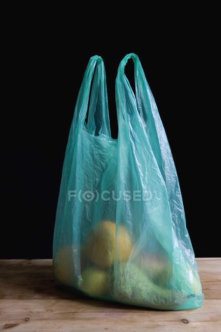 Fruit in plastic shopping bag on kitchen counter — Stock Photo