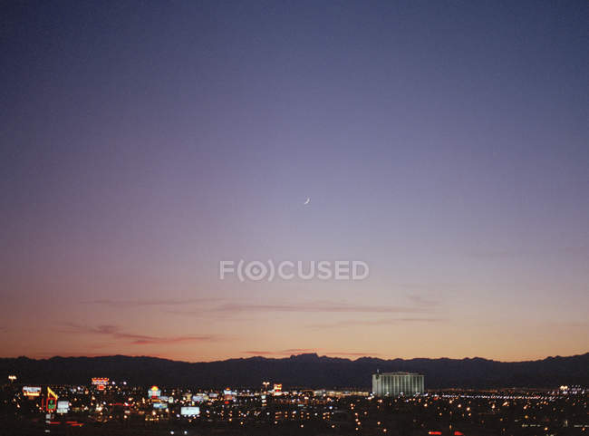 Scenic view to cityscape at night and mountains silhouettes in distance over sunset sky — Stock Photo