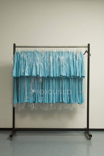 Row of blue shirts hanging on clothes rack — Stock Photo
