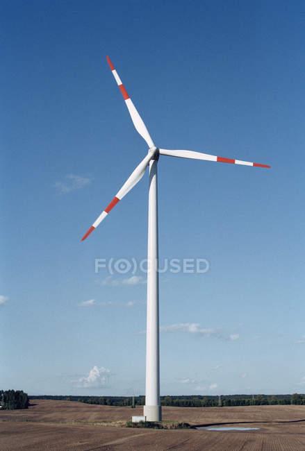 Éolienne en champ sur ciel bleu — Photo de stock