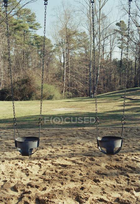 Balançoires pour deux enfants dans le parc ensoleillé — Photo de stock