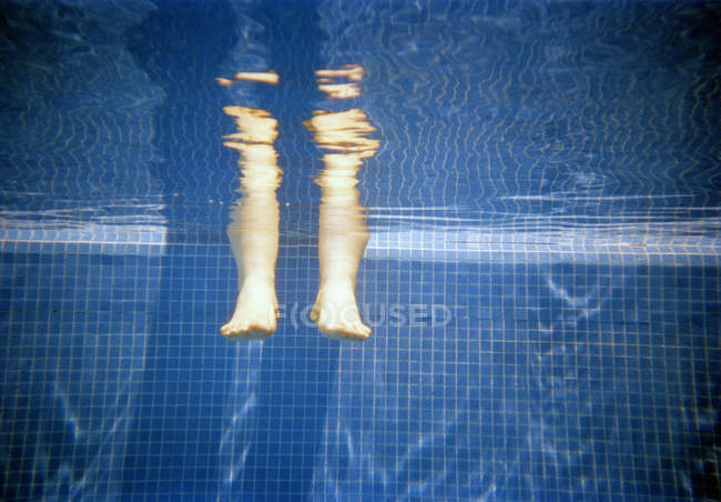 Legs in water at edge of swimming pool — Stock Photo