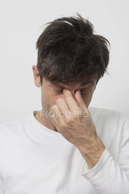 Close-up of man with sinus headache in front of white background — Stock Photo